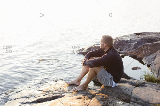 Sweden, Stockholm Archipelago, Sodermanland, Orno, Mature man sitting on rocky lakeshore