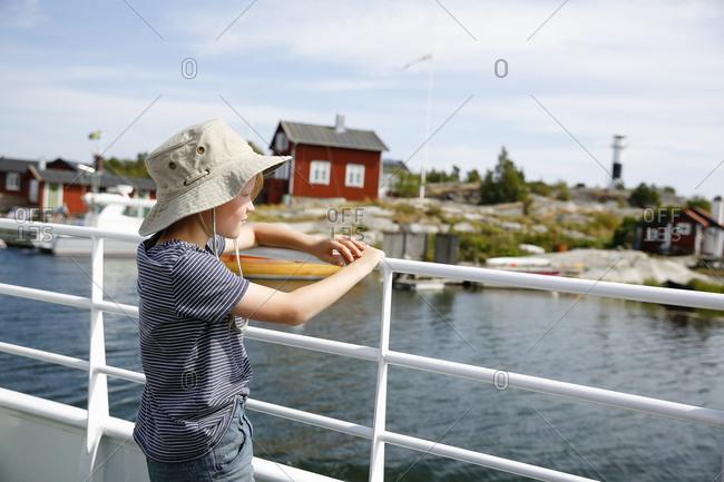 Sweden, Stockholm Archipelago, Sodermanland, Orno, Blonde boy leaning on railing by sea
