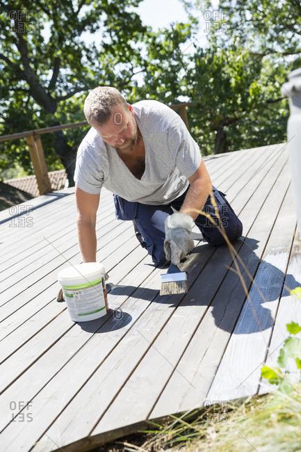 Sweden, Stockholm Archipelago, Sodermanland, Orno, Mature man painting porch