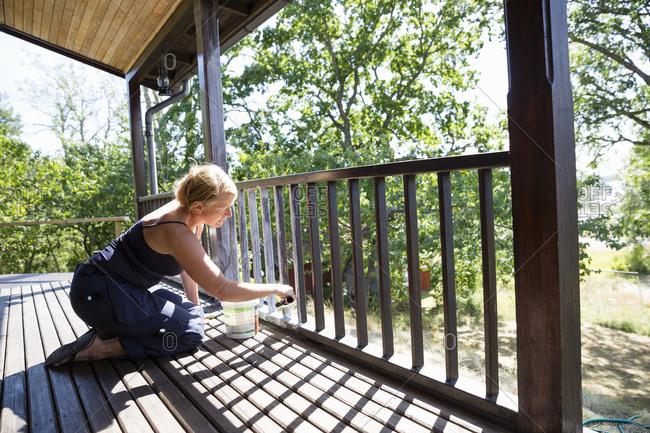 Sweden, Stockholm Archipelago, Sodermanland, Orno, Mature woman painting porch railing