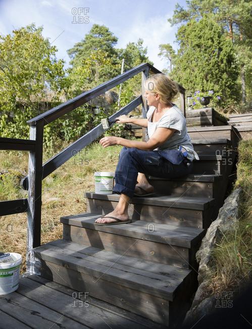 Sweden, Stockholm Archipelago, Sodermanland, Orno, Mature woman painting wooden railing
