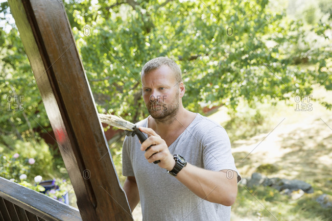 Sweden, Sodermanland, Stockholm Archipelago, Orno, Mature man painting wooden porch column
