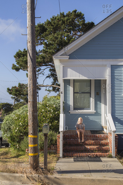 USA, California, Pacific Grove, Girl sitting on steps in front of blue house