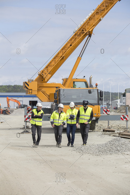 Sweden, Halland, Kungsbacka, Construction workers walking with crane in background