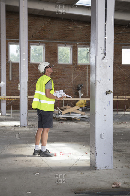 Sweden, Man standing in construction site and holding papers