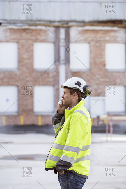 Sweden, Man using smartphone in construction site