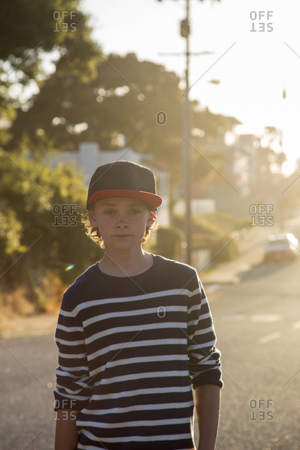 USA, California, Pacific Grove, Portrait of boy standing in street at sunset