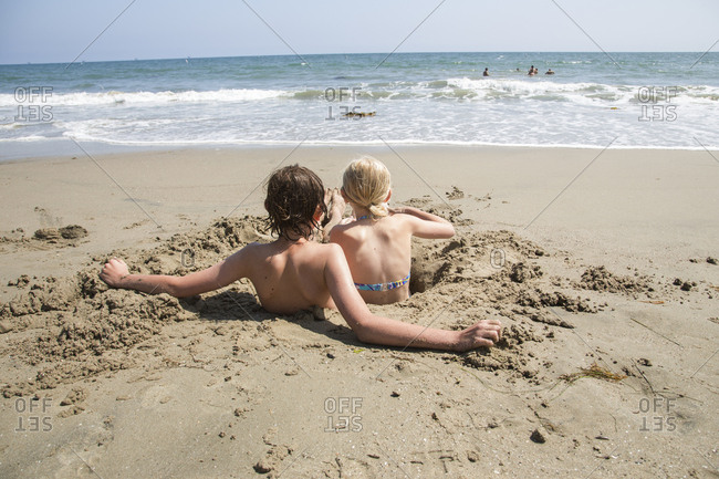 USA, California, Santa Barbara, Boy and girl in hole in sand on beach