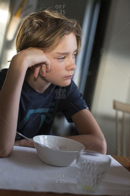 Sweden, Boy sitting at table with bowl and glass