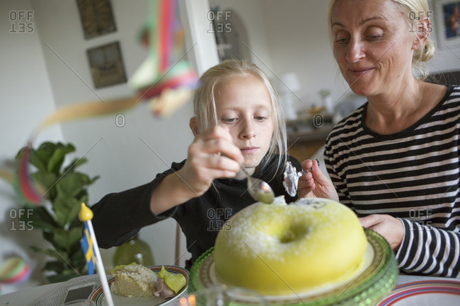 Sweden, Girl and mature woman cutting birthday cake