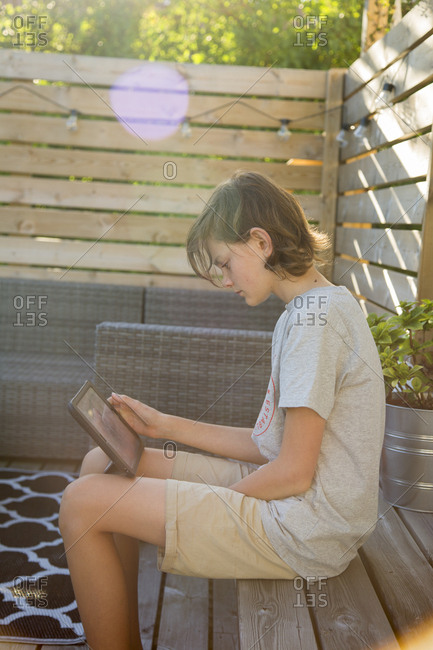Sweden, Boy using tablet on wooden terrace