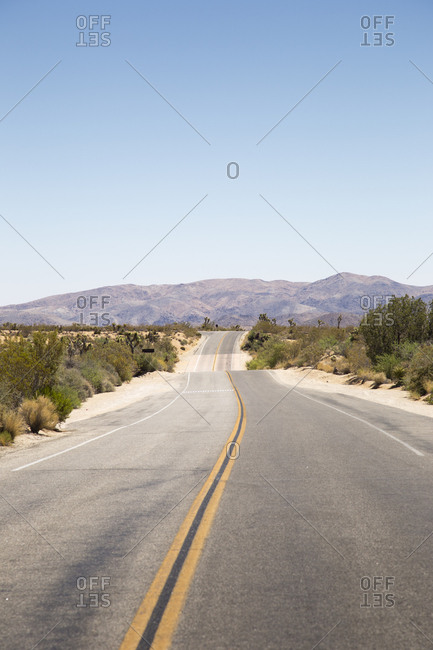 USA, California, Joshua Tree, Road leading towards mountain range on horizon