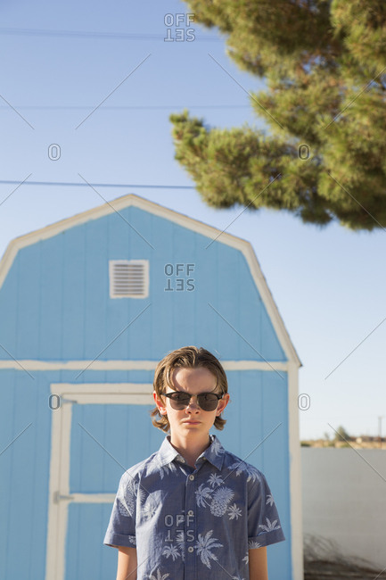USA, California, Boy wearing sunglasses standing in front of blue barn