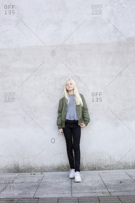 Sweden, Portrait of girl standing against concrete wall