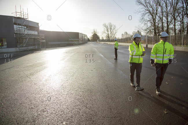 Sweden, Mature men wearing protective workwear in street outside construction site