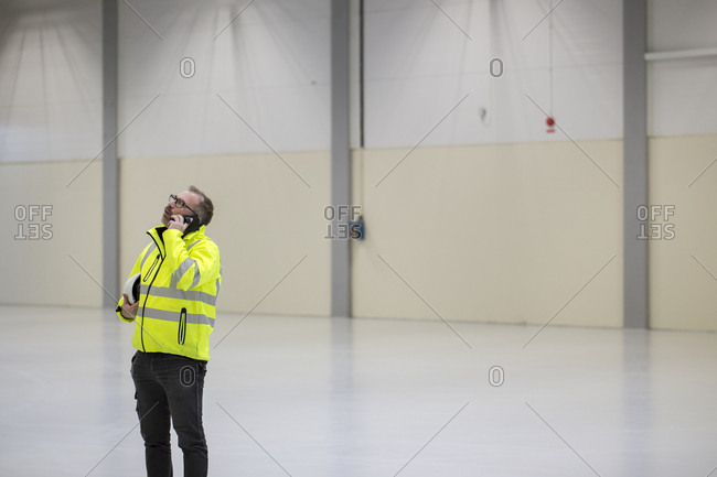 Sweden, Mature man wearing protective workwear talking on telephone in industrial hall
