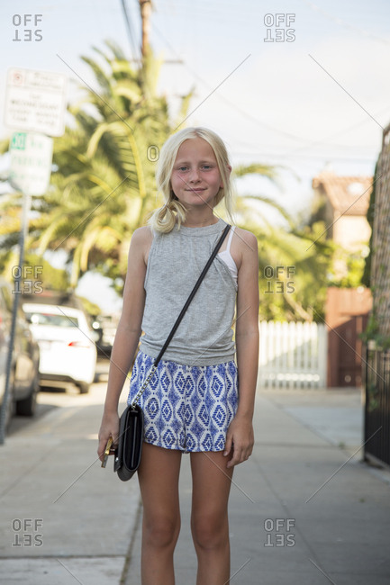 USA, California, San Diego, Portrait of girl standing in street with palm tree in background