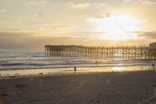 USA, California, San Diego, Beach and pier backlit by sunlight