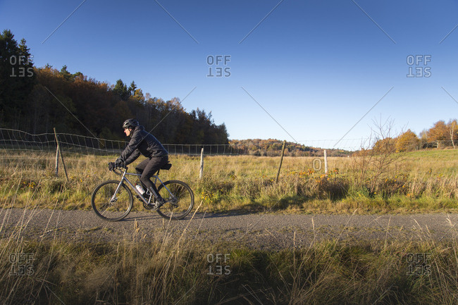 Sweden, Vastergotland, Lerum, Mature man riding bicycle on dirt road among pastures and forests