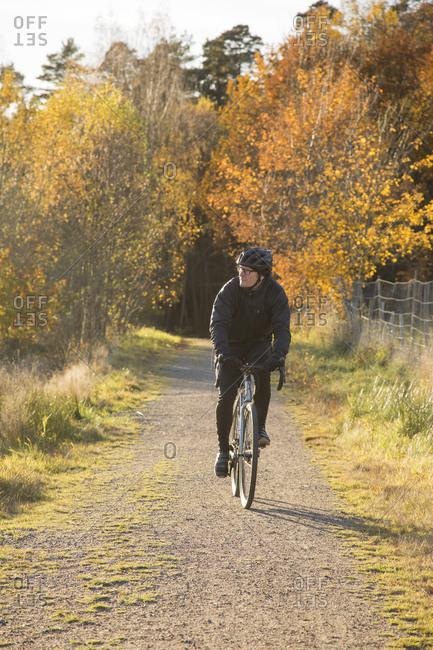 Sweden, Vastergotland, Lerum, Mature man riding bicycle on dirt road through autumn forest