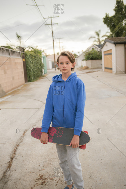 USA, California, San Diego, Portrait of boy holding skateboard
