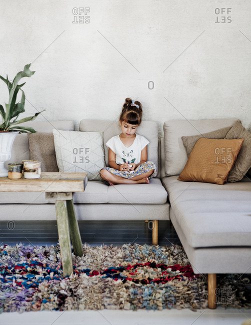Sweden, Girl sitting on sofa