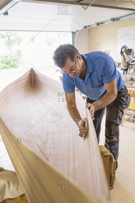 Sweden, Man building wooden rowboat