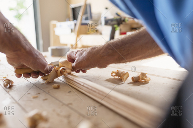 Sweden, Man planning wood in workshop