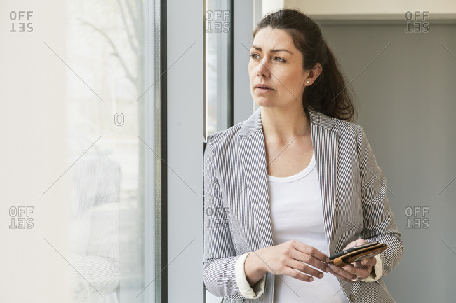 Sweden, Businesswoman looking through window