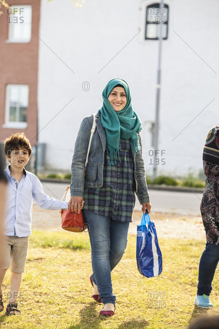 Sweden, Blekinge, Solvesborg, Young woman and boy walking holding hands