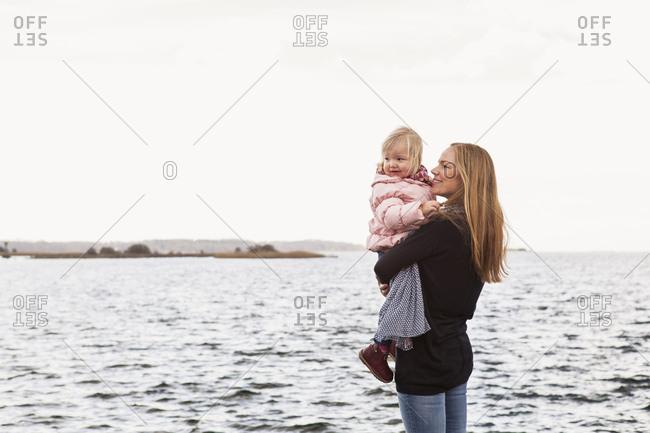 Solvesborg, Blekinge, Sweden, Mid adult woman holding girl at seashore
