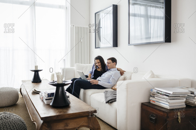 Germany, Man and woman sitting on sofa with laptop
