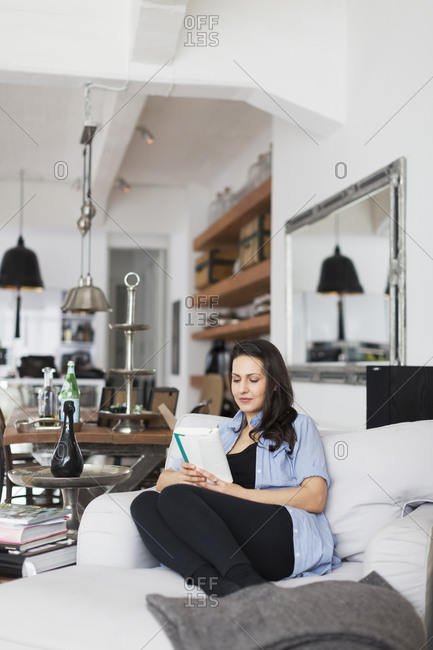 Germany, Woman reading in living room