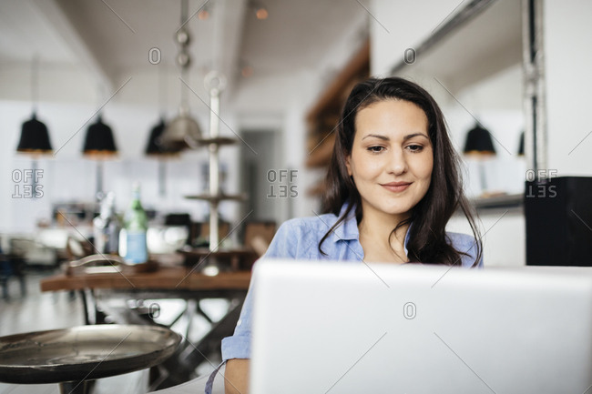 Germany, Pleased woman using computer