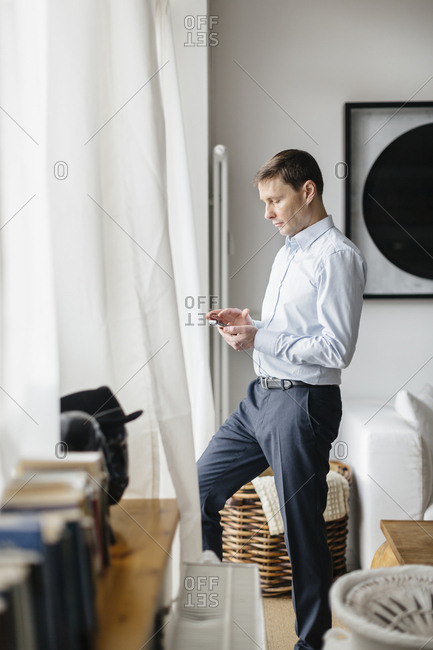 Germany, Man looking at mobile phone by window