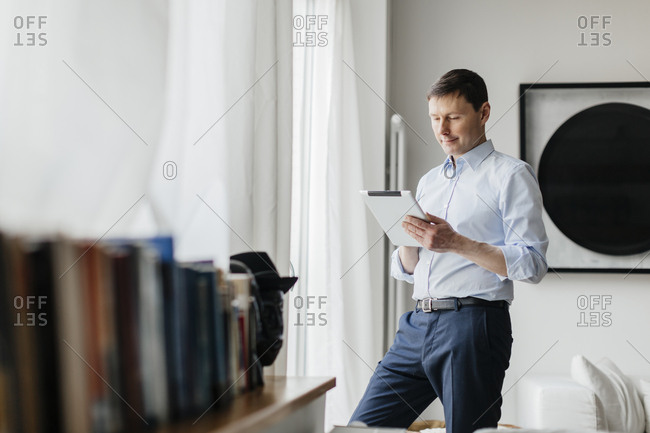 Germany, Man using tablet by window