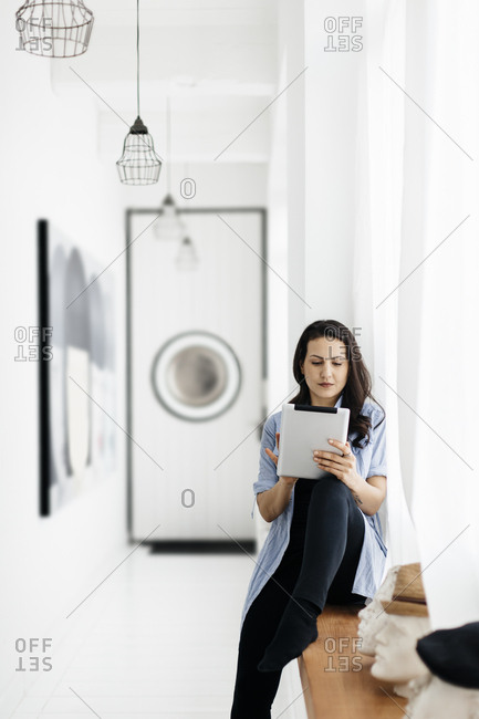 Germany, Woman sitting on window sill and using tablet