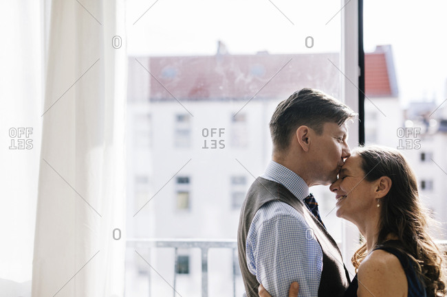Germany, Couple hugging by window
