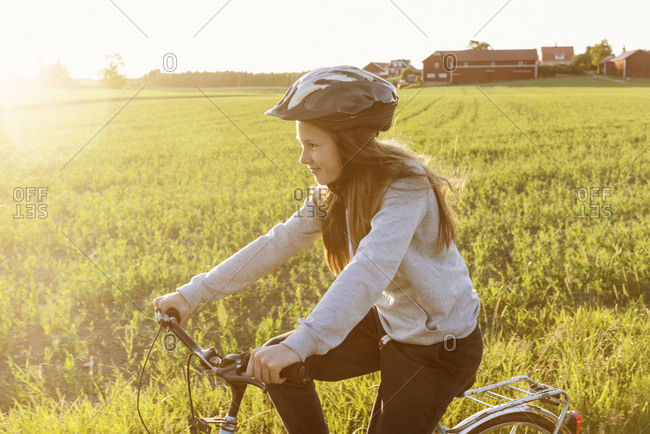 Sweden, Sodermanland, Girl cycling against field