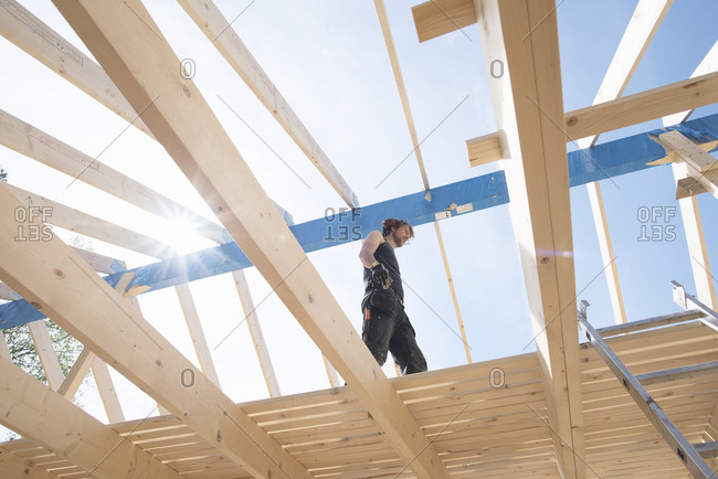 Sweden, Sodermanland, Low angle view of carpenter working on construction site