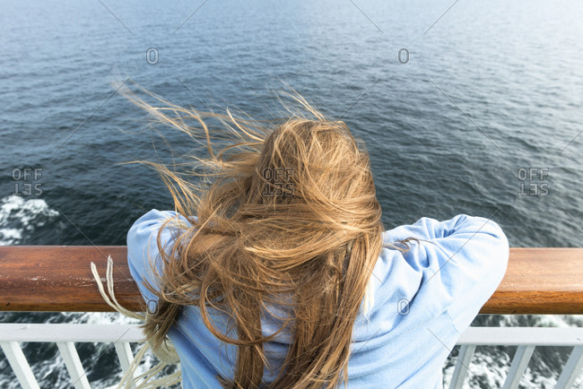Sweden, Sodermanland, Rear view of blonde girl leaning on railing on cruise ship
