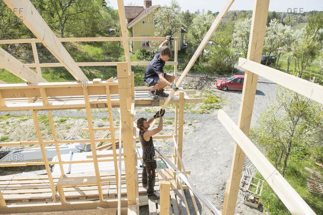 Sweden, Sodermanland, Mid adult men constructing wooden building