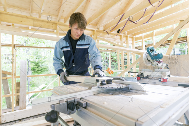 Sweden, Sodermanland, Mid adult man cutting wood with electric saw