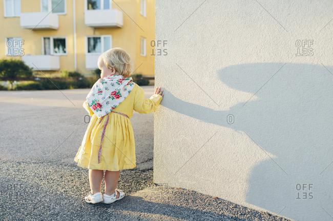 Sweden, Blekinge, Karlskrona, Girl leaning against wall