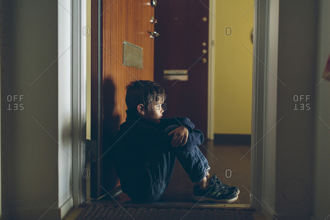 Sweden, Blekinge, Karlskrona, Boy sitting on floor next to door