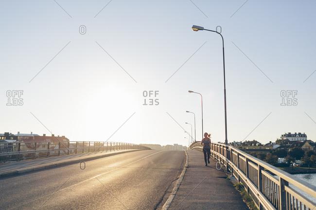 Sweden, Blekinge, Karlskrona, Young woman jogging on bridge