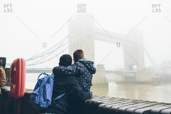UK, England, London, Mid adult man holding boy while looking at Tower Bridge in fog