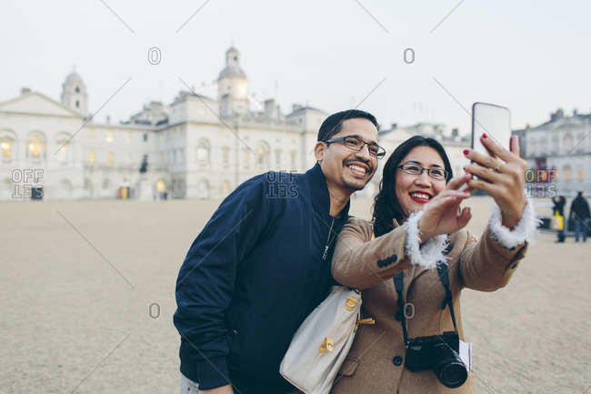 UK, England, London, Mid adult man and woman taking selfies with Horse Guards Parade in background