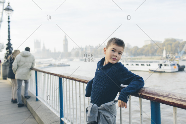 UK, England, London, Boy posing on shore of River Thames with fog covered Houses of Parliament in background