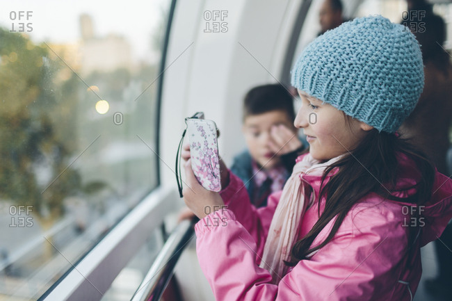 UK, England, London, Girl taking pictures with smart phone and boy inside London Eye